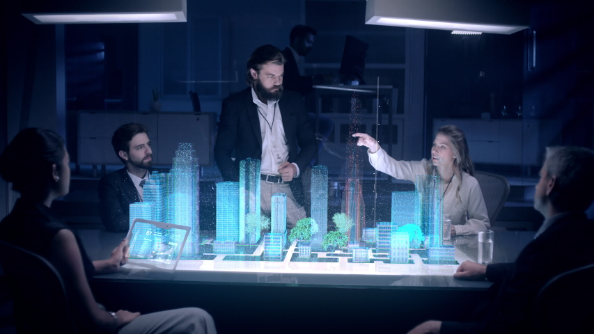 In the Near Future: Businessman in Suit presenting Architecture Project to Colleagues and Partners sitting around Futuristic Table with Holographic Modern Augmented Reality Technology.