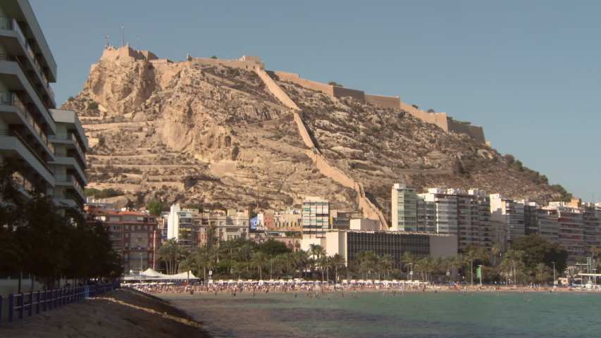 People enjoying at beach against Santa Barbara Castle on mountain in Alicante during sunny day