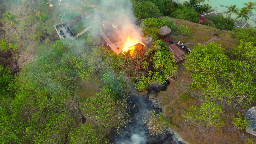 Aerial of a straw hut burning on a beautiful tropical island, Fireman with Hose Putting Out Flames - Bora Bora, French Polynesia | Shutterstock HD Video #1041608818