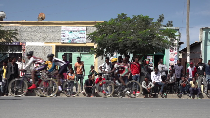 MEKELE, ETHIOPIA – MARCH 2019: Slow motion of crowds watching speed bicycle riders during local competition near Mekele, sports in Ethiopia