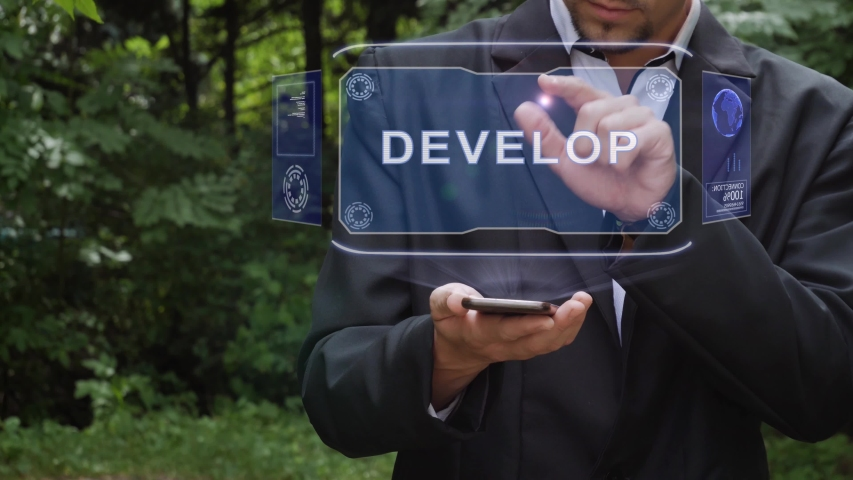 Unrecognizable businessman activates conceptual HUD holograms on smartphone with text Develop. Bearded man in a white shirt and a jacket with a holographic screen on a background of green trees | Shutterstock HD Video #1041620368