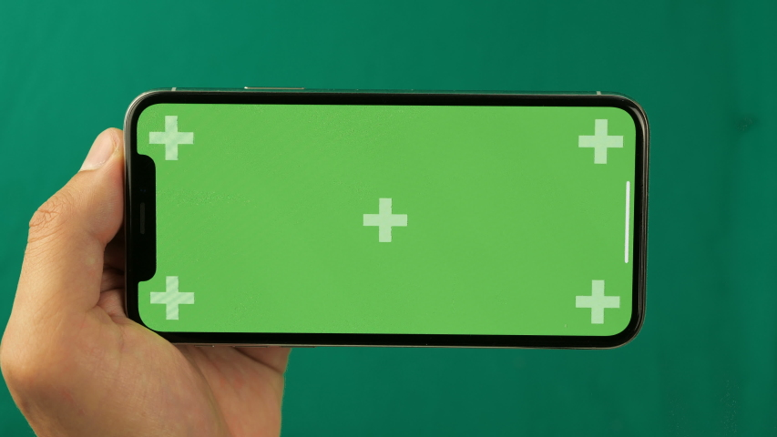Kiev, Ukraine - November 23, 2019: Horizontal smartphone in the hand closeup isolated at green background. Phone screen is green chroma key, background with another chroma key green screen.