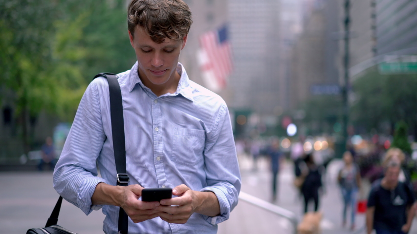 Young employer in formal wear reading sms message on modern mobile phone standing at urban setting in downtown and using 4g wireless internet connection for communicate with colleagues  | Shutterstock HD Video #1041632077