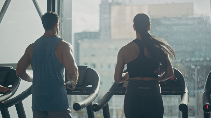 Male and Female Couple Exercising on Treadmills, Doing Fitness Exercise. Muscular Athletes Actively Training in the Modern Gym. Sports People Workout in Luxury Fitness Club. Back View Slow Motion Royalty-Free Stock Footage #1041637675