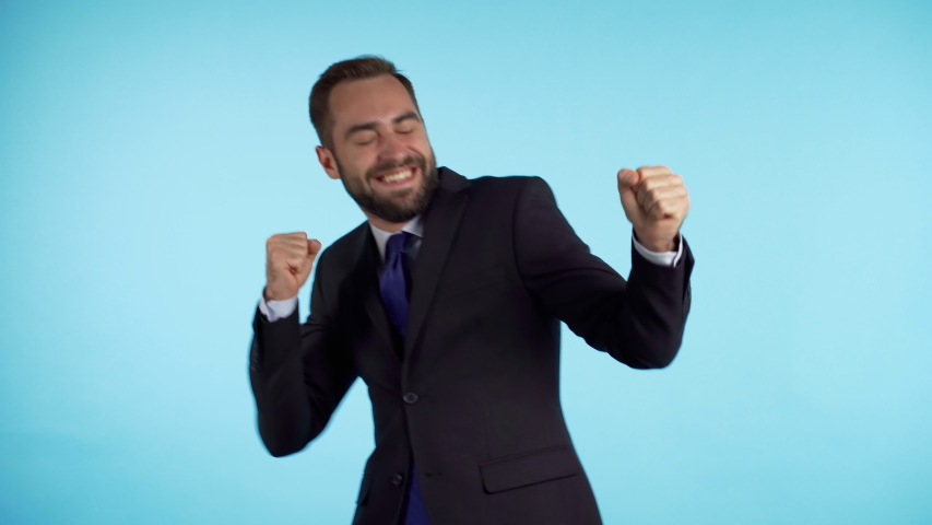 Surprised excited happy businessman funny dancing on blue background. Man shows yeah gesture of victory, he achieved result, goals.