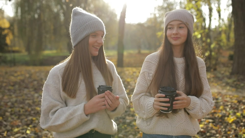 Teen girl in the park with coffee in her hands, happy childhood | Shutterstock HD Video #1041663082