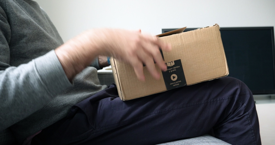 Paris, France - Circa 2019: Side view of curious man unboxing Amazon Prime e-commerce cardboard box with Brita XXL package with 12 water filter cartridges and glass jar - time-lapse fast motion