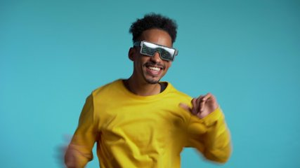 African american man in glowing glasses dancing with hands isolated on blue background. Party, music, lifestyle, radio and disco concept.