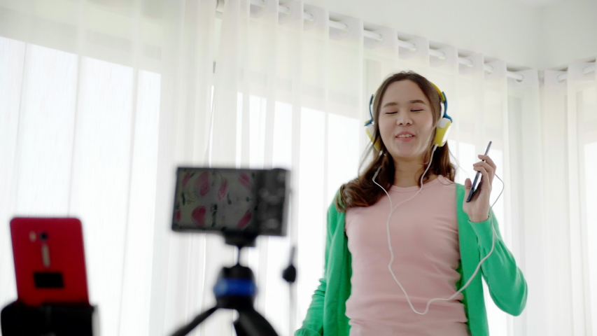 Asian women beautiful bloggers wear colourful clothes Such as green, pink Standing and dancing in headphones. Communicate sales to customers via live video. Online selling business via social media | Shutterstock HD Video #1041670798