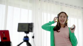 Asian women beautiful bloggers wear colourful clothes Such as green, pink Standing and dancing in headphones. Communicate sales to customers via live video. Online selling business via social media