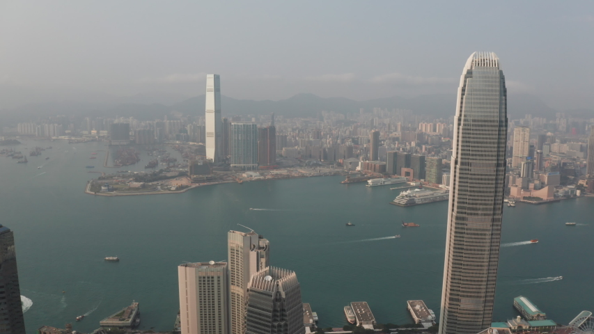 Aerial drone 4k video over Hong Kong Victoria Harbor at sunset time. dolly shot drone camera movement at Central distinct of Hong Kong Island, Hong Kong