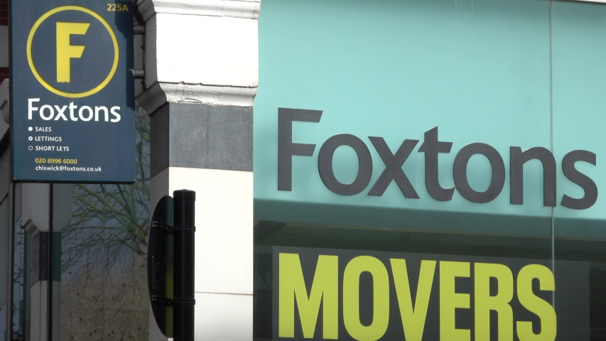 LONDON , - - / United Kingdom (UK) - 03 13 2019: Zoom out from Foxtons estate agents sign on Chiswick High Road, London. | Shutterstock HD Video #1041679552