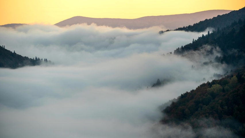 Beautiful sunrise in foggy mountains. Timelapse of running mist in green mountains early in the morning. 4K, UHD #1041683239