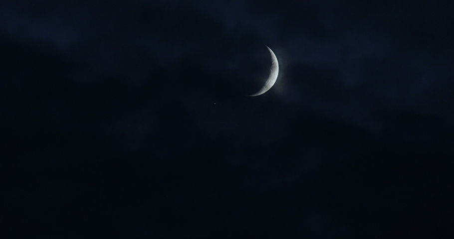 Clouds pass by the moon, winds blow during the storm.Details on the surface .A Crescent moon on a dark, cloudy night.  in a creepy feeling like a horror Thriller movie.dark night sky, black clouds. Royalty-Free Stock Footage #1041684796