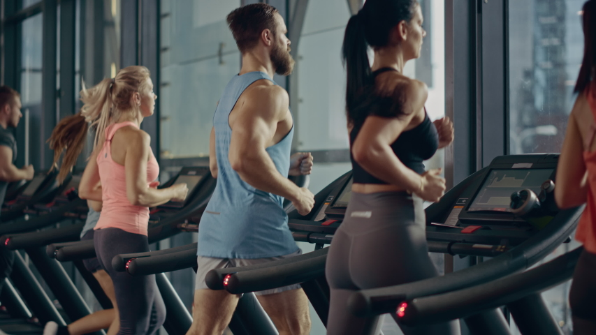 Athletic People Running on Treadmills, Doing Fitness Exercise. Athletic and Muscular Women and Men Actively Training in the Modern Gym. Sports People Workout. Back View Elevating Camera