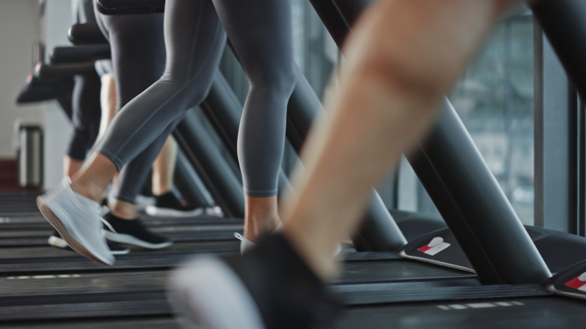 Beautiful Athletic Sports Woman Wearing Wireless Headphones, Listens to a Podcast or Sport Music Playlist while Running on a Treadmill. In Background Fit Athletes Training in the Gym Royalty-Free Stock Footage #1041686698
