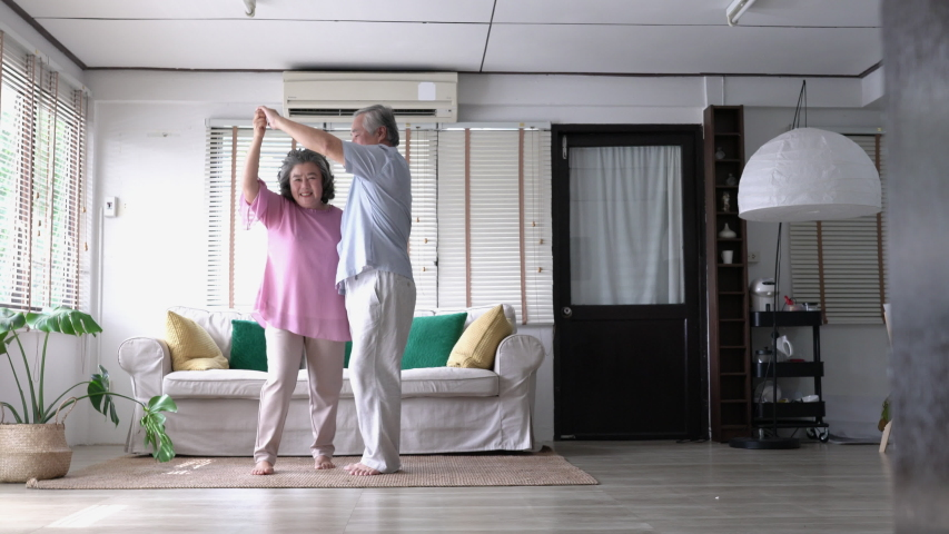 Happy asian mature senior couple dancing laughing in living room at home. Beautiful romantic middle aged older grandparents relaxing fun together celebrating anniversary enjoy care love tenderness.