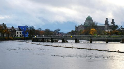 Galway, Ireland. View of roman catholic cathedral of Galway, Ireland during the rainy day in autumn. River and cloudy sky, zoom out