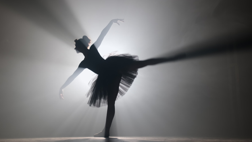 Professional ballerina dancing ballet in spotlights smoke on big stage. Beautiful young girl wearing black tutu dress on floodlights background. Black and white. 4k