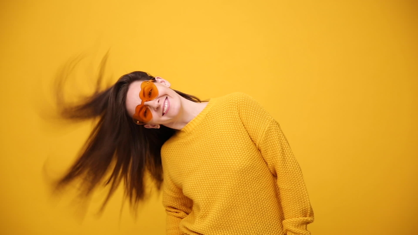 Smiling fun beautiful brunette young woman in bright yellow sweater shirt posing dancing fluttering hair isolated over yellow orange background in studio. People sincere emotions, lifestyle concept. | Shutterstock HD Video #1041695176
