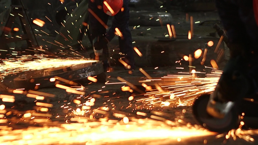 Male hand cuts off pieces of water pipe with angle grinder. Cutting of a steel with splashes of sparks at construction site. Sparks during cutting of metal angle grinder | Shutterstock HD Video #1041699577