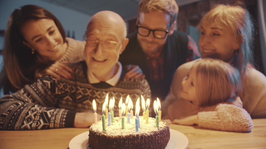 Celebration and family concept - happy grandfather blowing candles on birthday cake at dinner party surrounded by his large family. | Shutterstock HD Video #1041705808