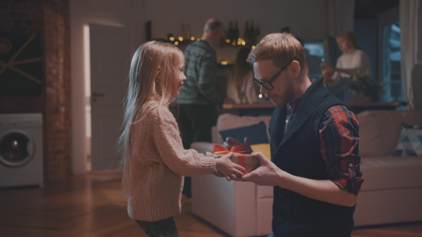 Cute little girl embracing her father and giving him New Year present. Young father receiving birthday present from his little daughter. Family celebrating thanksgiving together. | Shutterstock HD Video #1041705877
