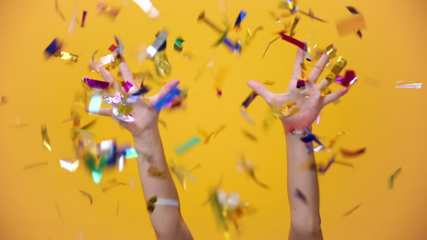 Flying falling colorful confetti isolated over yellow orange background in studio. Holiday party birthday lifestyle Happy New Year 2020 concept. Woman toss up golden shine tinsel show thumbs up.