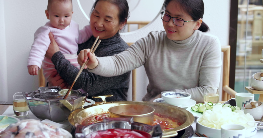 Slow motion of happy Chinese family of three generation having lunch together in the restaurant senior woman holding her baby granddaugher with her daughter eating hotpot Sichuan food at Chengdu China