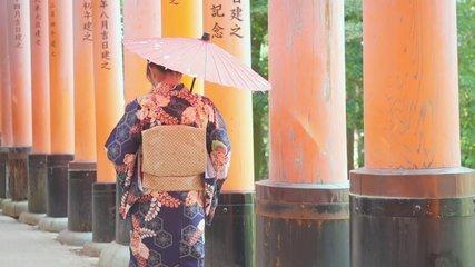 slow motion Geishas girl wearing Japanese kimono walking  red wooden Tori Gate at Fushimi Inari Shrine in Kyoto, Kimono is a Japanese traditional garment.