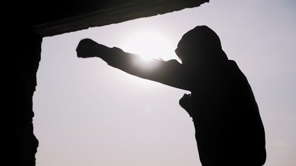 Silhouette of a boxer on a sunset background. Coaches punches. Shadow-boxing. Outdoor workout. Motivational video.