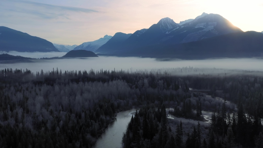 Aerial: sunrise view over forest, rocky mountains and the Blue River. Fog is covering the forest and it feels tranquil. Blue River, British Columbia, Canada