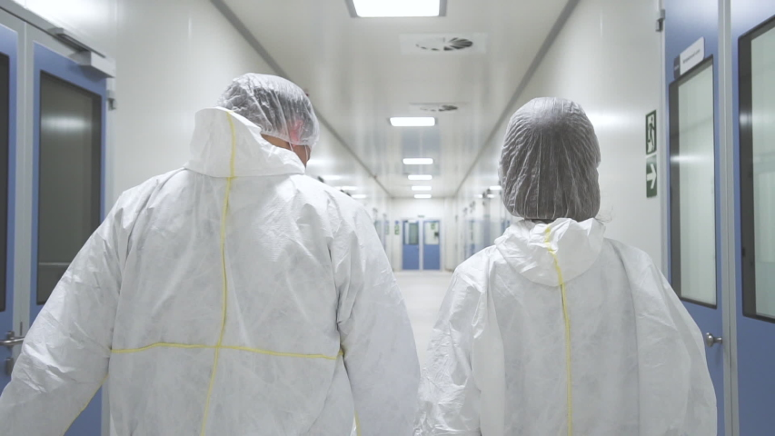 American man and woman worker walk and having talk in pharmaceutical plant. Two people employee discussing work ideas in interior of medical company. Back view of young staff wearing white protective | Shutterstock HD Video #1041766501