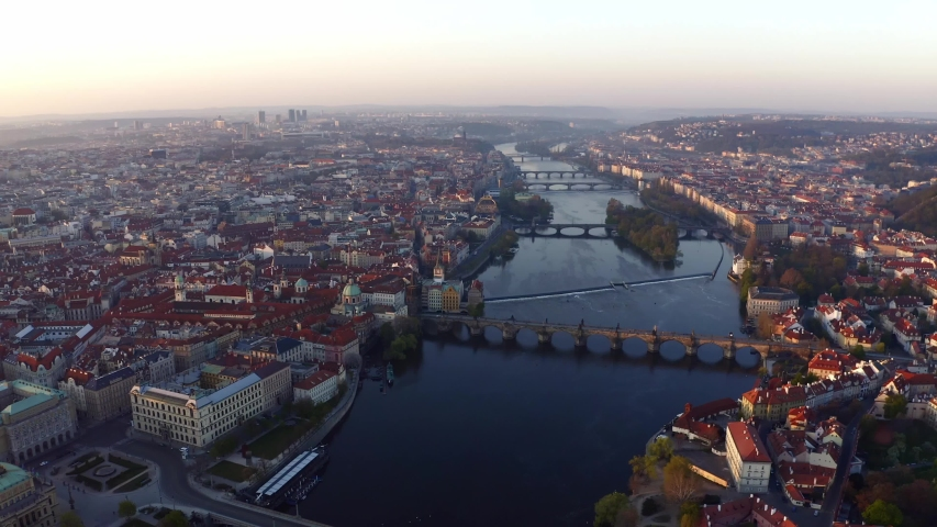 Wide shot Vltava river and bridges in Prague at sunrise. Picturesque cityscape from high above Vltava river, lateral motion over water and bridges, buildings with red tiled roof on both sides | Shutterstock HD Video #1041773413