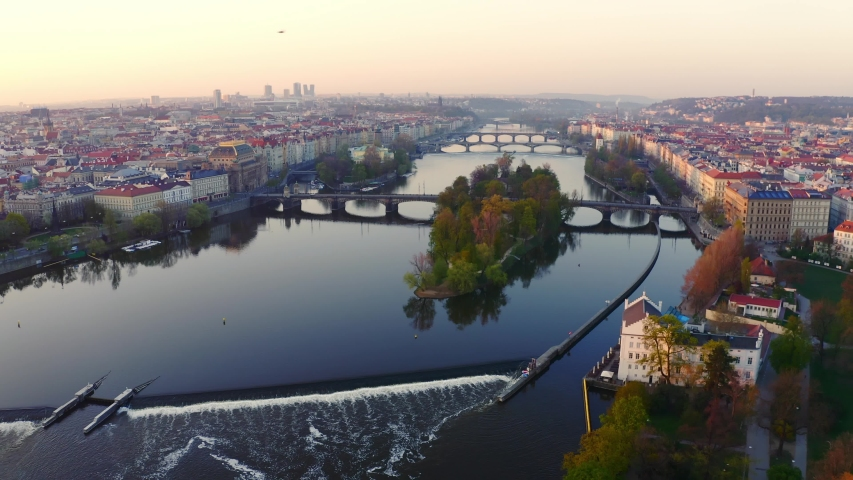 Aerial view Vltava river and bridges in Prague at sunrise. Picturesque cityscape from high above Vltava river, drone flying over still water with reflections bridges and buildings at calm morning | Shutterstock HD Video #1041773422