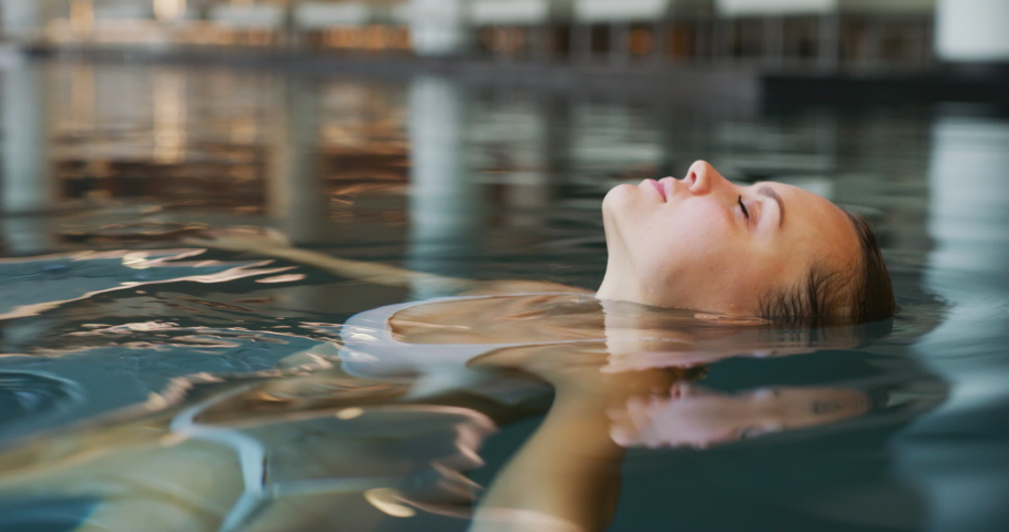 Close up of an young woman is enjoying and having relax in an indoor illuminated with night lights swimming pool in a luxury wellness center.