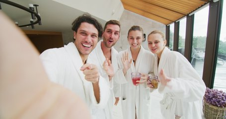 The young happy couples in white bathrobes are making a selfie or a video call after various treatments in a luxury wellness center.