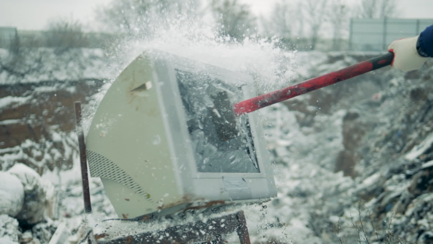 White TV is smashed with hammer at a landfill. Man with a hammer shatters the TV screen. | Shutterstock HD Video #1041792628