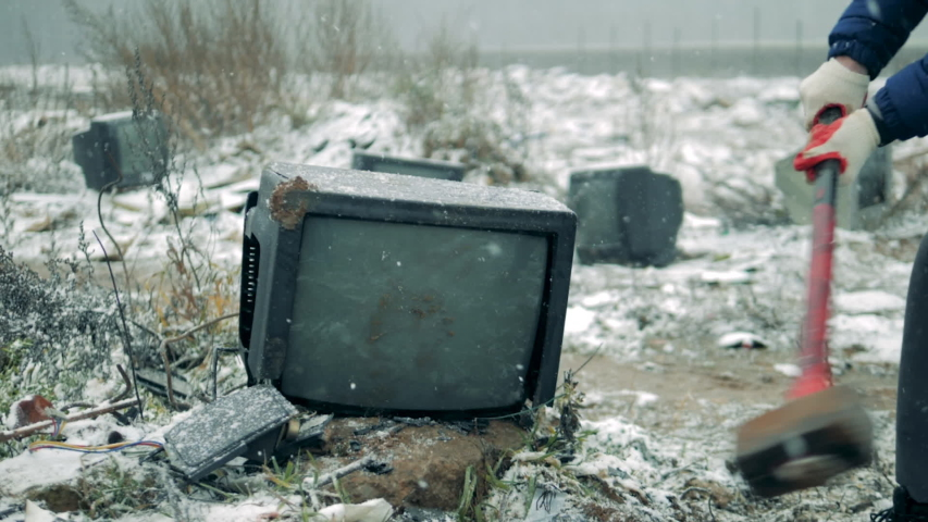Person breaks a TV with a hammer at a dump. Man with a hammer shatters the TV screen. | Shutterstock HD Video #1041792676