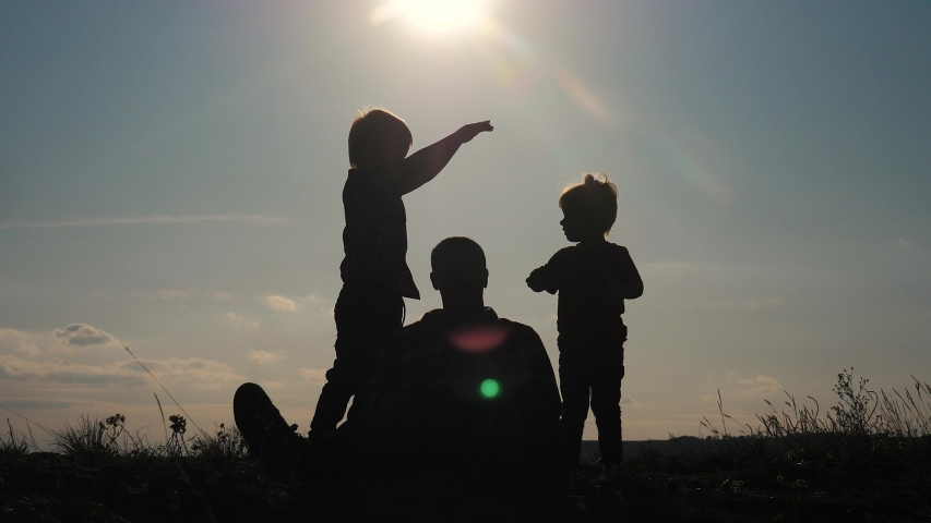 Happy family teamwork silhouette shows a house and comfort symbol at sunset. father dad and kids children portray a house roof hold their hands over their lifestyle heads | Shutterstock HD Video #1041794299