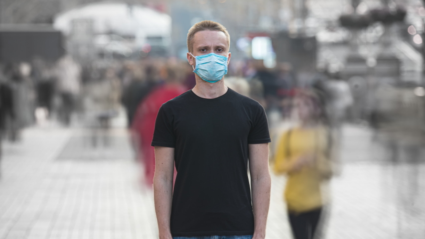 The young man with medical face mask stands in the crowdy flow. time lapse | Shutterstock HD Video #1041797164