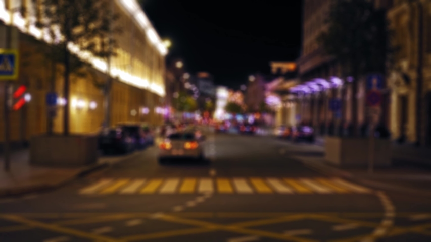 Time Lapse. Defocused view of a busy city street. Night. Heavy traffic. Bright, colorful, illuminated building facades. Parked cars. Pedestrians cross the road at a pedestrian crossing. Timelapse 4K