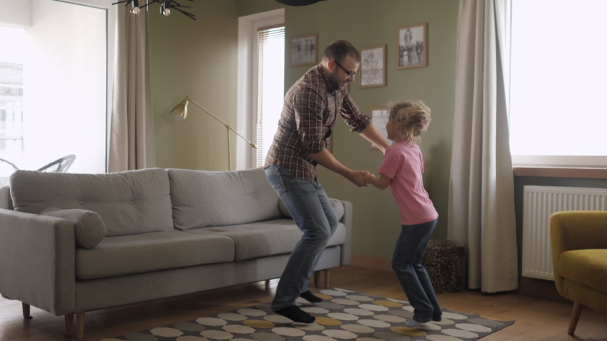 Young Father and Her Daughter Playing in Living Room. Funny Happy Family Father and Daughter are Dancing hold hands and jump at Home. Love Lifestyle Home. Slow Motion. | Shutterstock HD Video #1041823744