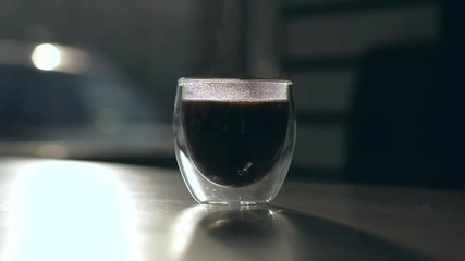 Cinematic video - silhouette of fresh coffee cup with steam rising in cafeteria. Slowmotion.