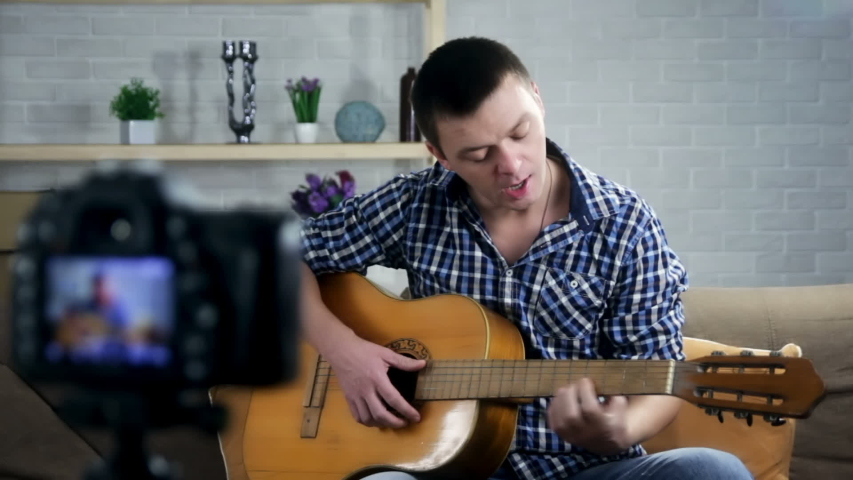 Learning guitar. Male music blogger sitting at home and recording new guitar lesson for Youtube channel. | Shutterstock HD Video #1041836899