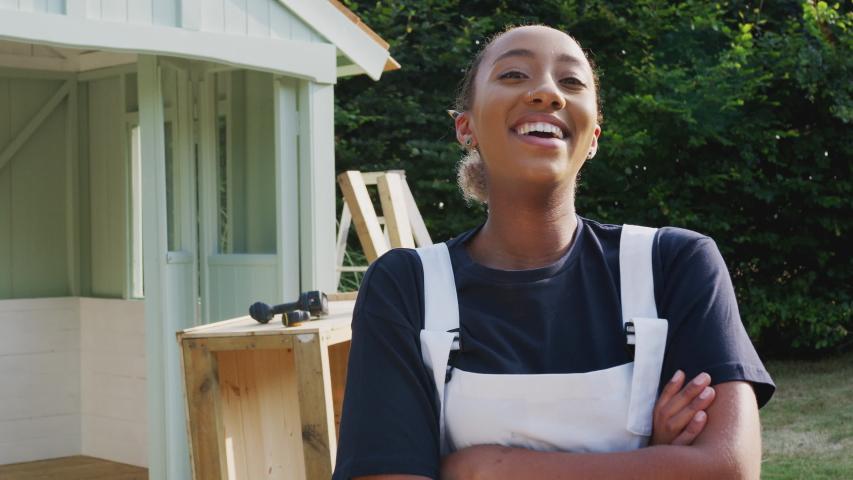 Portrait Of Female Carpenter Building Outdoor Summerhouse In Garden | Shutterstock HD Video #1041836938