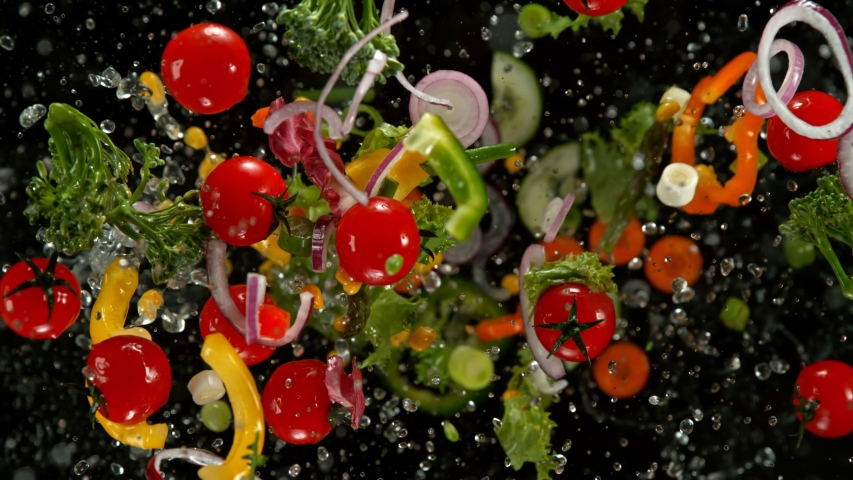 Super Slow Motion Shot of Flying Cuts of Colorful Vegetables and Water Drops on Black background at 1000fps. | Shutterstock HD Video #1041849979