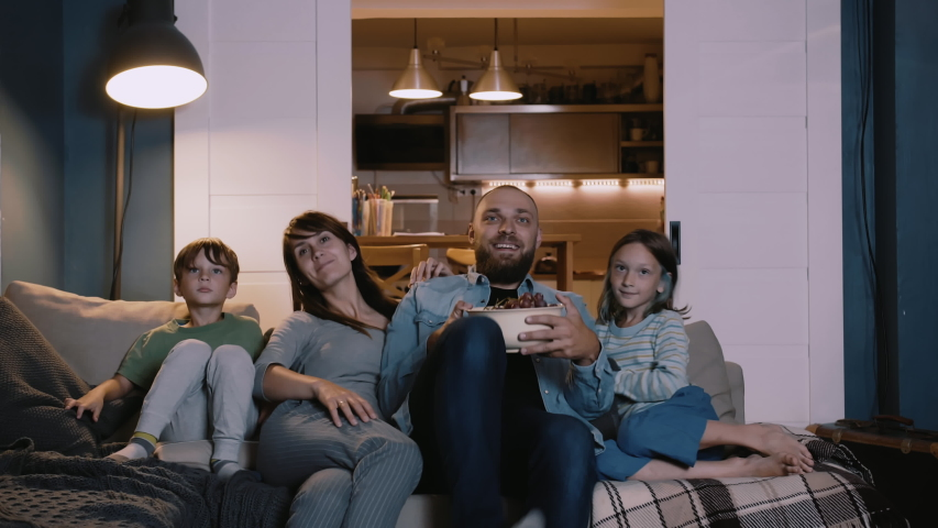 Happy young European family with two kids gather on couch to watch TV at home smiling. Togetherness and entertainment. | Shutterstock HD Video #1041877690