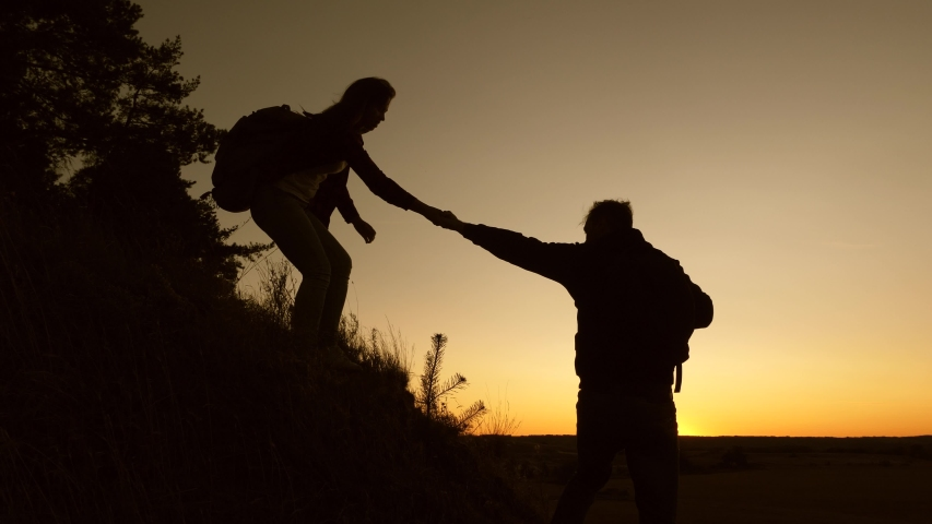 Travel and adventure concept. male traveler and female traveler descend from top of hill. teamwork of business people. tourists descend from the mountain in the sunset, one after another. | Shutterstock HD Video #1041880690
