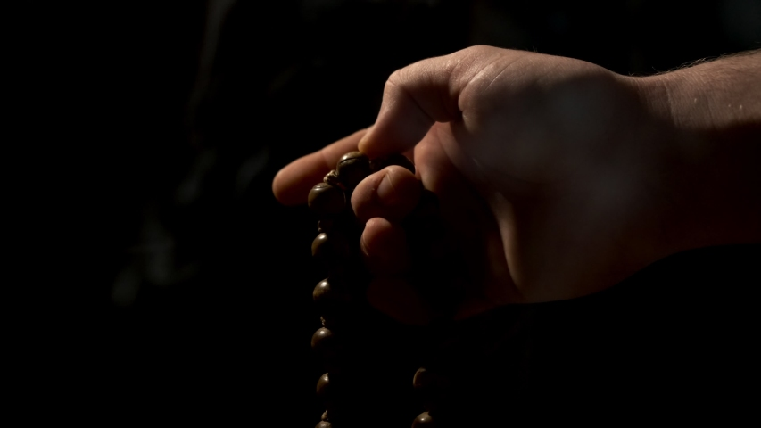 A hand slowly moves up eastern style chanting beads against a dark background with incense smoke rising in the foreground.   Shutterstock HD Video #1041882511